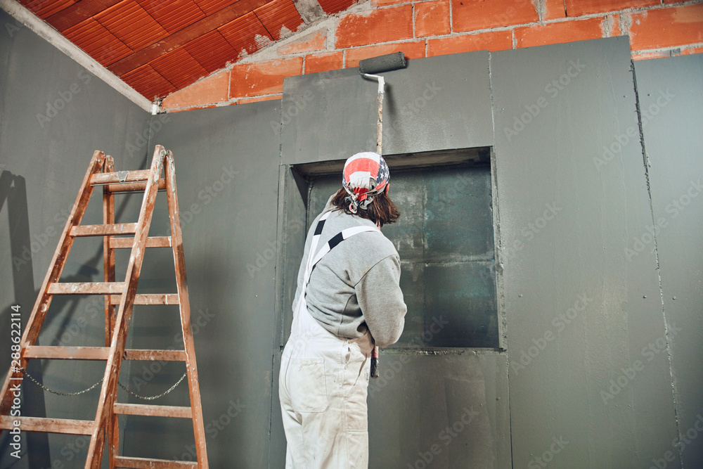 Fototapety, obrazy: Painter painting walls with a extender roller indoors.