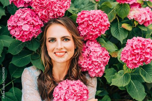 Fotografia, Obraz  Outdoor portrait of beautiful woman posing in pink hydrangea flowers, wearing bl