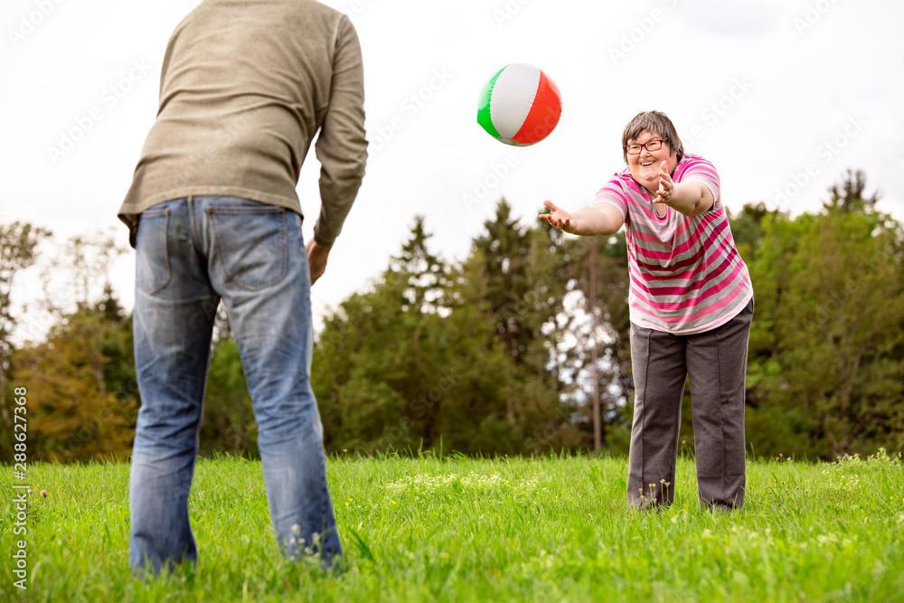 Fototapeta Geistig behinderte Frau spielt mit einem Ball, Geschicklichkeit und Konzentration durch Spiele
