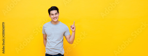 Fotografia, Obraz  Smiling young handnsome Asian man pointing hand up to copy space aside