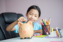 Happy Little Asian Girl Putting Money Coin Into Piggy Bank Select Focus Shallow Depth Of Field