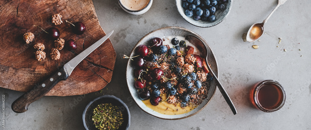 Fototapety, obrazy: Healthy vegan breakfast. Flat-lay of quinoa oat granola coconut yogurt bowl with fruit, seed, nut, berries and cup of coffee over table background, top view, wide composition. Clean eating food