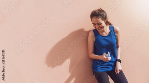 Poster Ecole de Yoga Asian beautiful women holding water bottle after play yoga and exercise on orange wall background with copy space.Exercise for Lose weight,increase flexibility and tighten the shape.