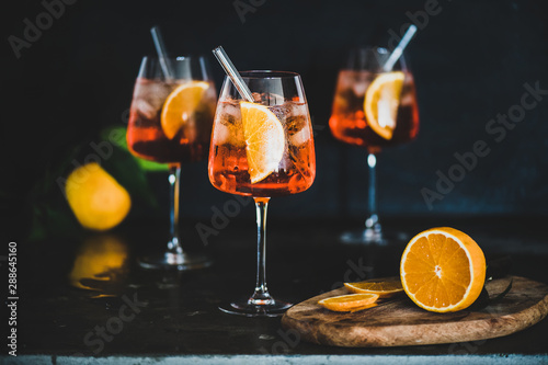 Aperol Spritz aperitif with oranges and ice in glass with eco-friendly glass straw on concrete table, black background, selective focus. Summer refreshing drink concept
