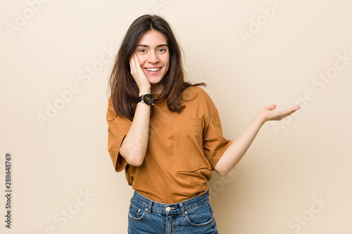 Young brunette woman against a beige background holds copy space on a palm, keep hand over cheek Wallpaper Mural