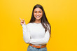 Young pretty arab woman against a yellow background smiling cheerfully pointing with forefinger away.