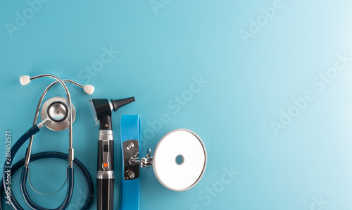 Pinturas sobre lienzo  Otoscope with stethoscope and reflector mirror on blue background