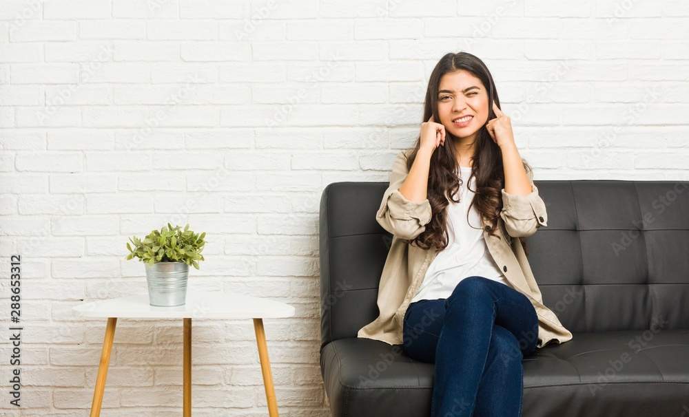 Fototapeta Young arab woman sitting on the sofa covering ears with hands.