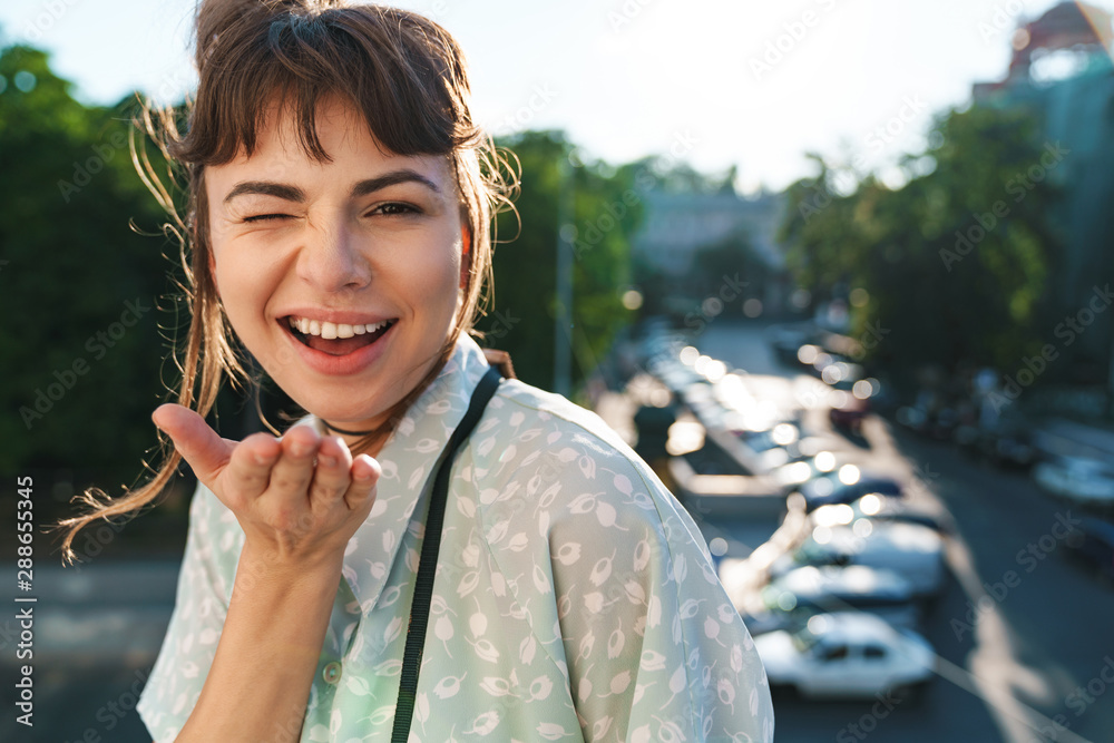 Fototapety, obrazy: Optimistic young beautiful woman photographer with camera on a balcony blowing kisses.