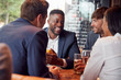 Group Of Business Colleagues Meeting For Drinks And Socializing In Bar After Work