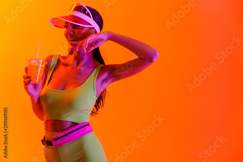 Emotional optimistic stylish girl in sport lifestyle clothes and transparent cap drinking juice cocktail isolated over orange background with neon lights Fototapeta