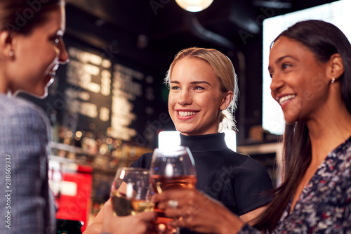 Three Women Making A Toast As They Meet For Drinks And Socialize In Bar After Wo Poster Mural XXL