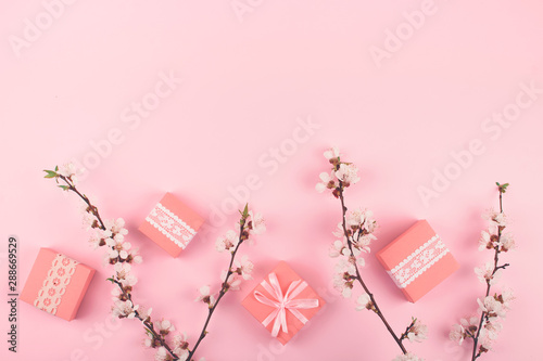 Obraz na plátně  Flat lay with pink gift boxes and blooming cherry sakura flowers on pastel background