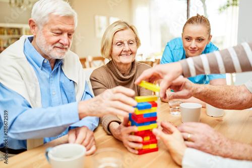Fotografie, Tablou  Gruppe Senioren spielt mit Bausteinen im Altenheim