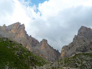 The peaks of the Dolomites of the Sassolungo Massif immersed in the clouds and in the nature of Trentino - Alto - Adige, Near the town of Canazei, Italy - August 2019.