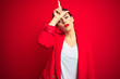 canvas print picture - Young beautiful business woman standing over red isolated background making fun of people with fingers on forehead doing loser gesture mocking and insulting.