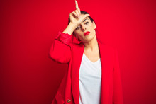 Young Beautiful Business Woman Standing Over Red Isolated Background Making Fun Of People With Fingers On Forehead Doing Loser Gesture Mocking And Insulting.