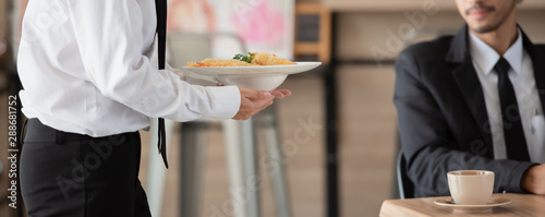 Fototapeta Waiter with plate of food in hand serving at table at restaurant, health care concept. obraz