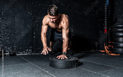 Valokuvatapetti Young strong sweaty focused fit muscular man with big muscles doing push ups wit