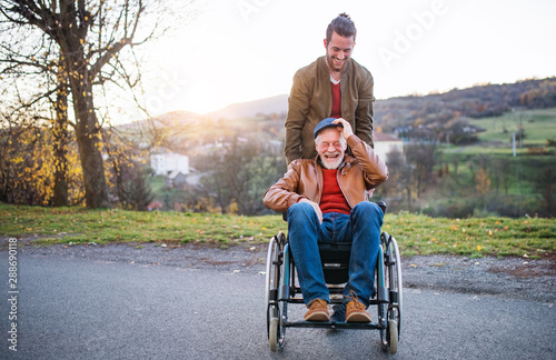 Papel de parede  Young man and his senior father in wheelchair on a walk in town.