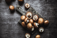 Royal Mushroom Champignons On A Old Wooden Cutting Board