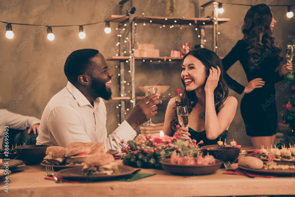 Fototapeta Profile side photo of cheerful couple of mixed-race man and chinese woman give toast hold champagne speak enjoy christmas party x-mas night in house with table full of newyear dinner feat indoors
