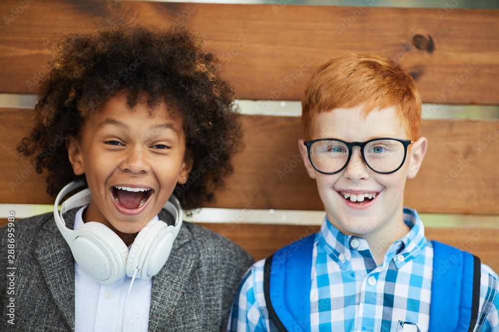 Fototapety, obrazy: Portrait of happy multiethnic two schoolboys smiling at camera over wooden background outdoors