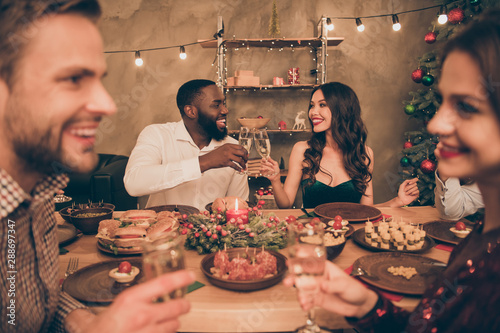 Nice attractive lovely smart stylish well-dressed cheerful cheery positive glad guys spending eve noel event clinking wineglasses greetings congrats over served table in decorated house