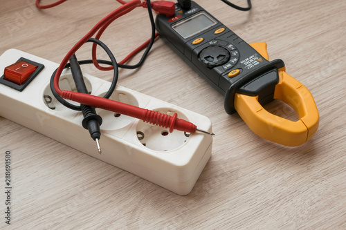 Photo Clamp meter with Power strip on the wooden table