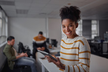 Cheerful Young African American Businesswoman In Casual Wear Holding Digital Tablet Smiling And Looking To Camera While Her Colleagues Communicating In The Background - Female Entrepreneur - Women