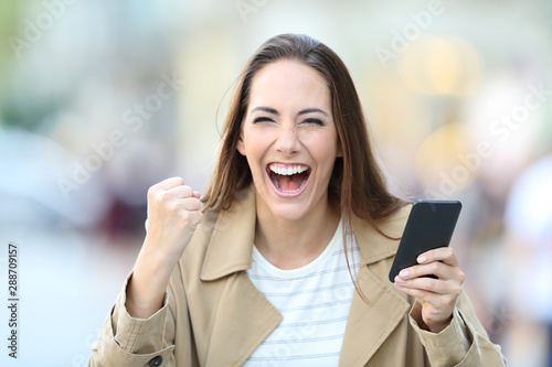 Photo sur Toile Les Textures Excited woman holding phone looking at camera