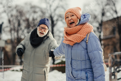 Papiers peints Glisse hiver Excited aged woman pulling hand of her husband and smiling