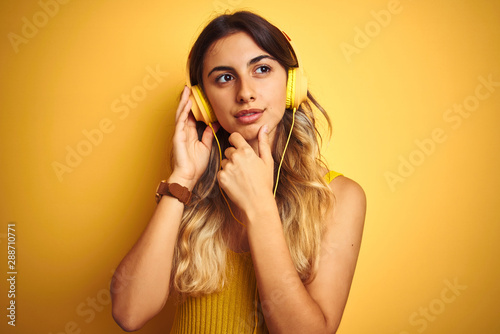 Young beautiful woman wearing headphones over yellow isolated background serious face thinking about question, very confused idea - 288710771