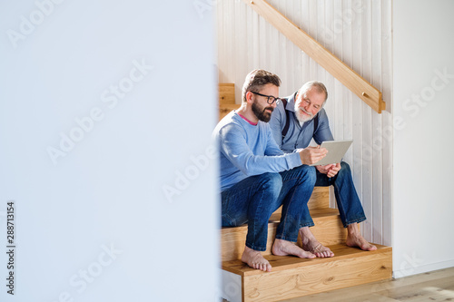 An adult son and senior father with tablet sitting on stairs indoors at home.