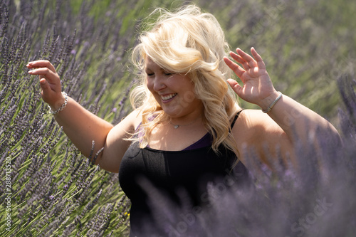 Valokuva Happy woman raises arms and laughs while sitting in a lavender field