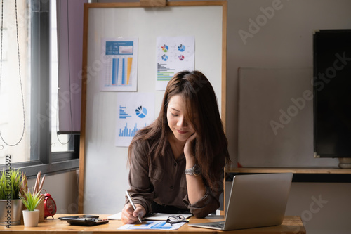 Fototapeta Businesswoman or Accountant hands holding paperwork with calculator, account and saving concept. obraz