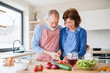 Leinwanddruck Bild A portrait of senior couple in love indoors at home, cooking.