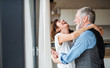 canvas print picture A senior couple indoors at home, laughing and hugging.
