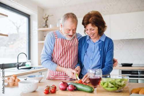 Ingelijste posters Eigen foto A portrait of senior couple in love indoors at home, cooking.