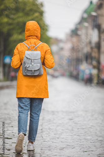 Obraz woman in yellow raincoat walking by city streets under rain - fototapety do salonu