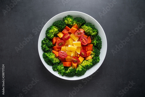 A plate of nutritious delicious fruit and vegetable salad on a black background Canvas Print