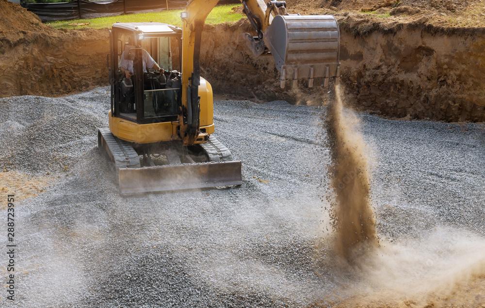 Fototapeta Excavator bucket moving gravel stones for foundation building