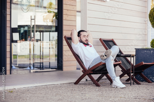 Fényképezés  Thoughtful young stylish hipster man with beard resting sitting on the lounge beside the hotel