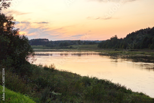 Foto op Aluminium Rivier Sunset by the river in the summer countryside