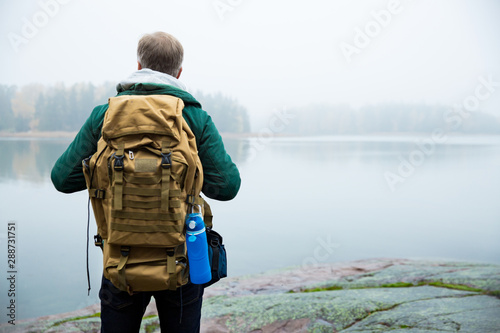 Obraz Mature man exploring Finland in the fall, looking into fog. Hiker with big backpack standing on mossy rock. Scandinavian landscape with misty sea and autumn forest. Back view - fototapety do salonu