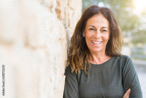 fototapeta na lodówkę Beautiful middle age woman smiling cheerful leaning on a brick wall at the city street on a sunny day