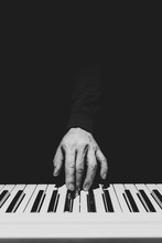 BW Male Musician Hand Playing On Piano Keys. Music Background