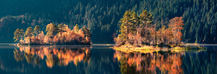 Fototapeta Rzeki i Jeziora Panoramic autumn view of Eibsee lake. Unbelievable morning scene with first sunlight glowing small islands on bottom of the Zugspitze peak, Bavaria, Germany, Europe.