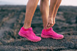 Leinwanddruck Bild - Fit run girl getting ready to walk on mountain rocsk tying up laces of trail running shoes - hot pink fashion footwear runner activewear lifestyle.