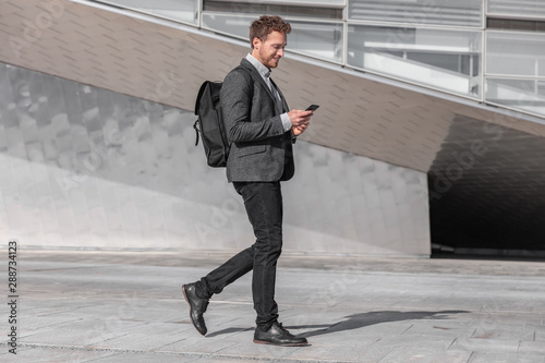 Obraz Happy young business man using phone walking on commute commuting to work with backpack bag on city street. Businessman texting looking at smartphone. - fototapety do salonu